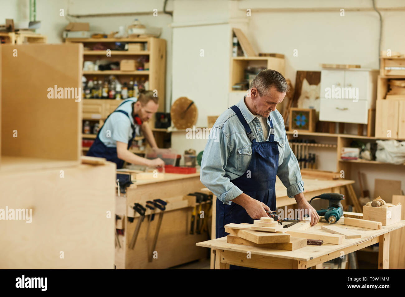 Portrait of two carpenters working with wood white assembling furniture in workshop, copy space - Stock Image
