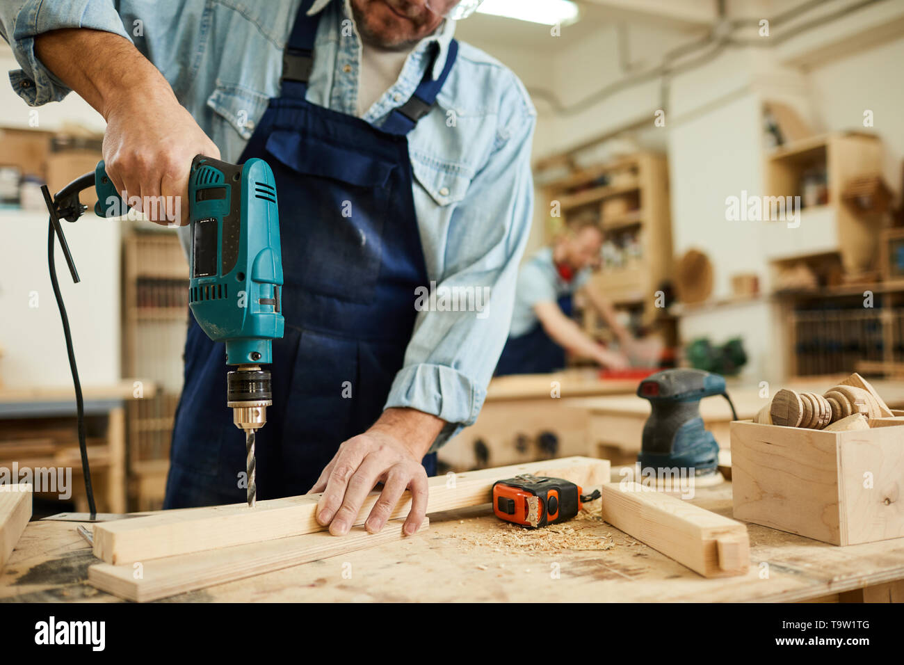 Closeup of mature carpenter drilling wood while working in joinery, copy space - Stock Image