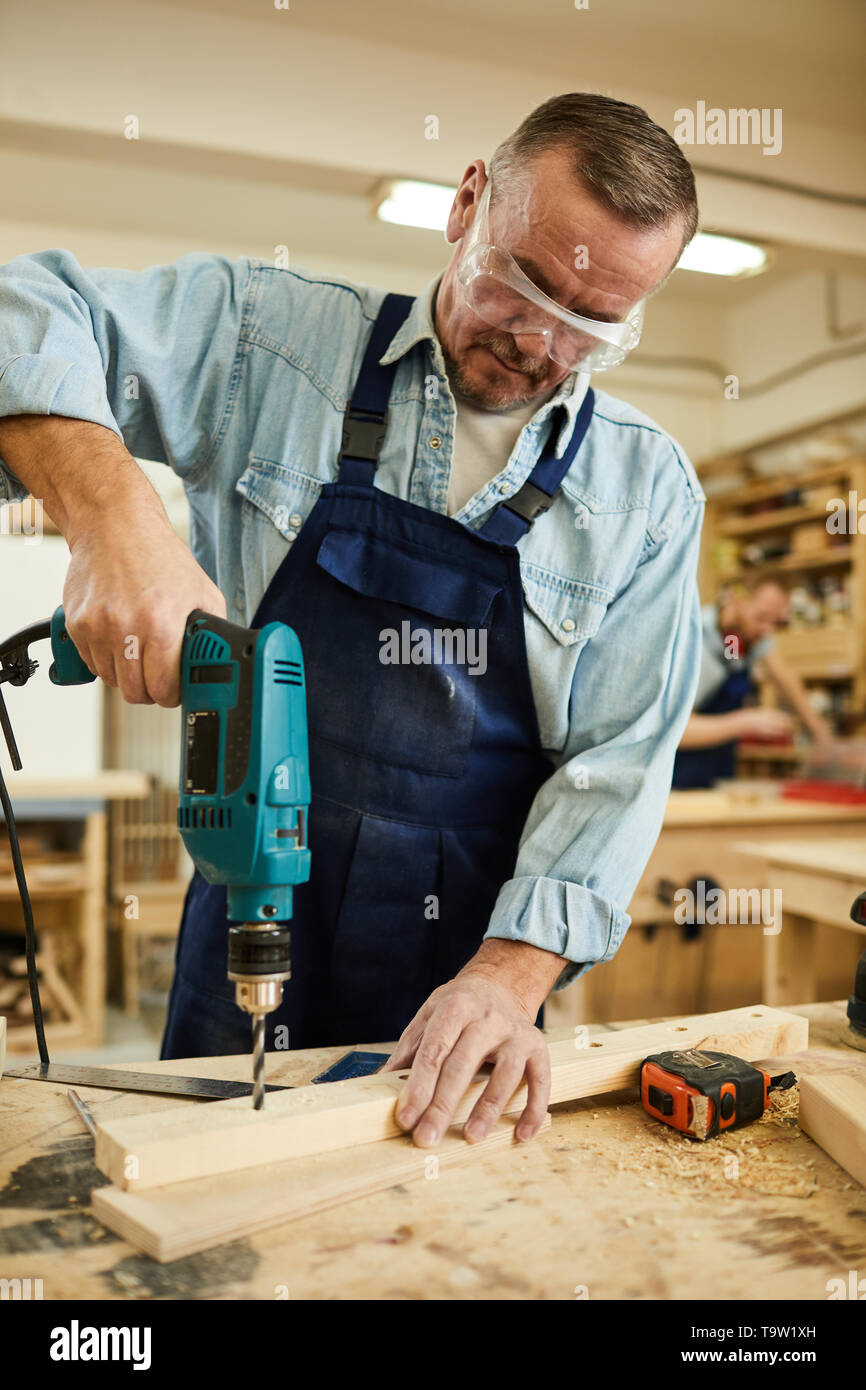 Portrait of mature carpenter drilling wood while working at table in joinery, copy space - Stock Image