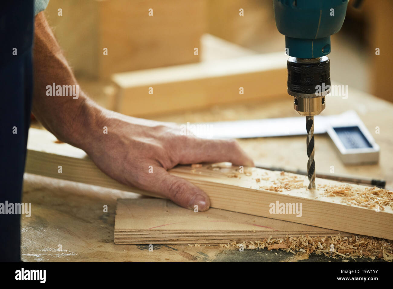 Closeup of unrecognizable carpenter drilling wood while working in joinery, copy space - Stock Image