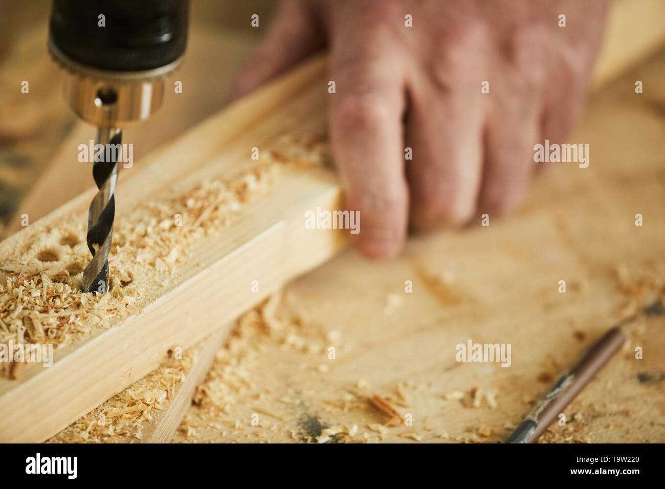 Extreme closeup of unrecognizable carpenter drilling wood while working in joinery, copy space - Stock Image