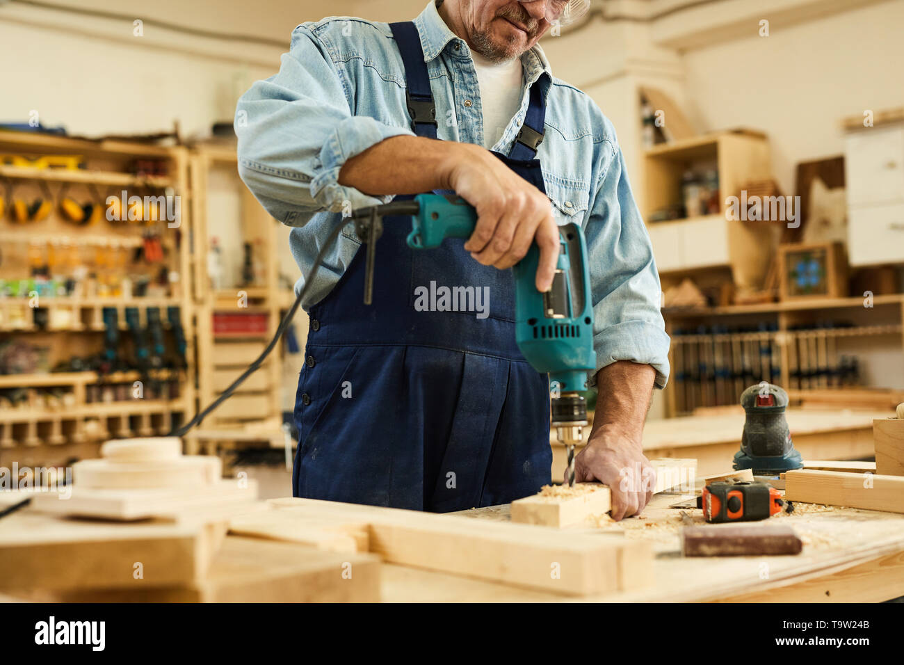 Mid section portrait of mature carpenter drilling wood while working in joinery, copy space - Stock Image