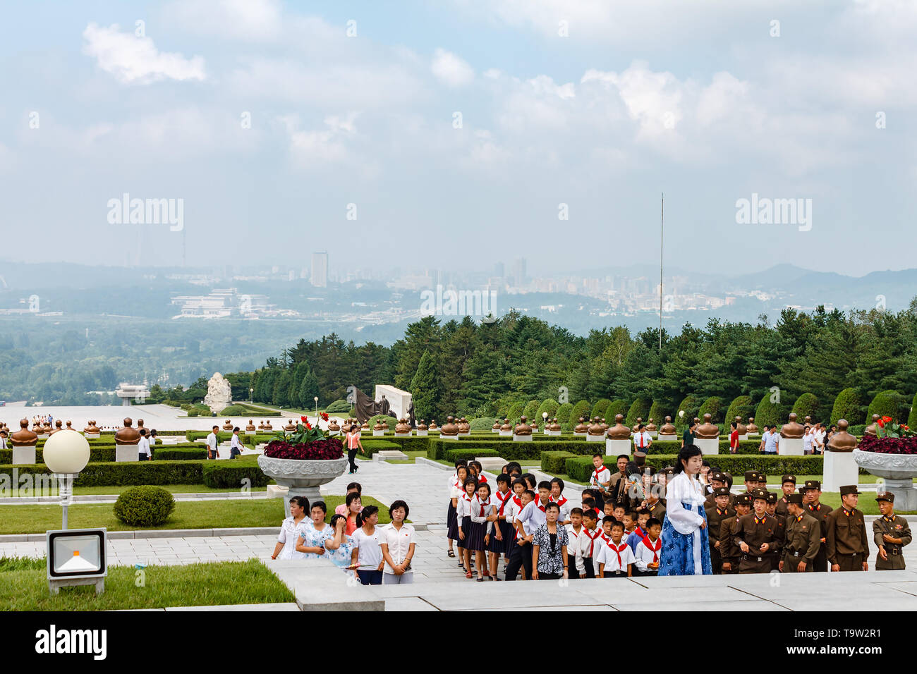 Pyongyang, North Korea - July 27, 2014: Korean schoolchildren and soldiers at the memorial cemetery of revolutionaries in Pyongyang. - Stock Image