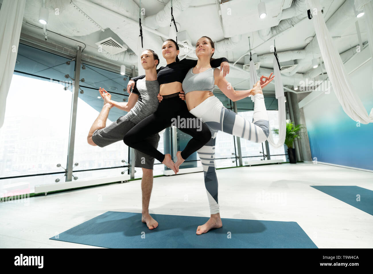 Women and one man doing nice yoga poses after practicing - Stock Image
