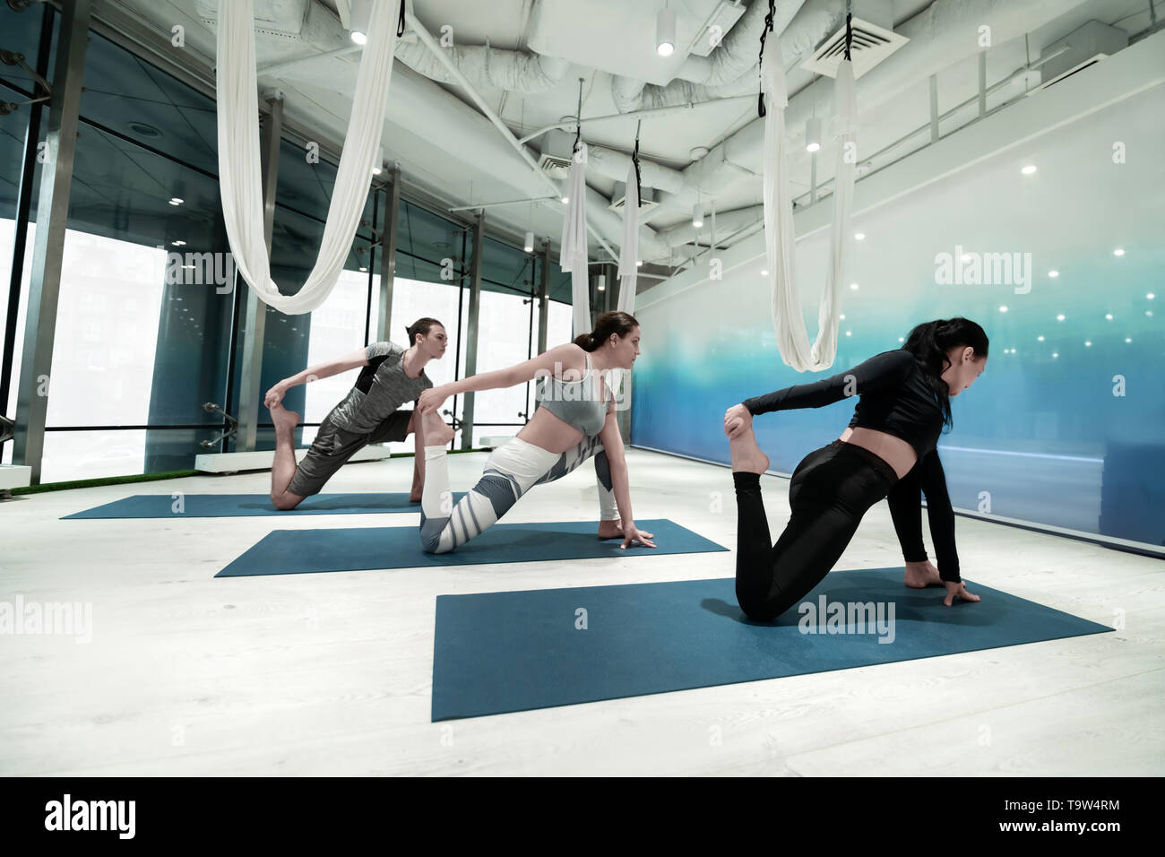 Women and man holding their foot while stretching doing yoga - Stock Image
