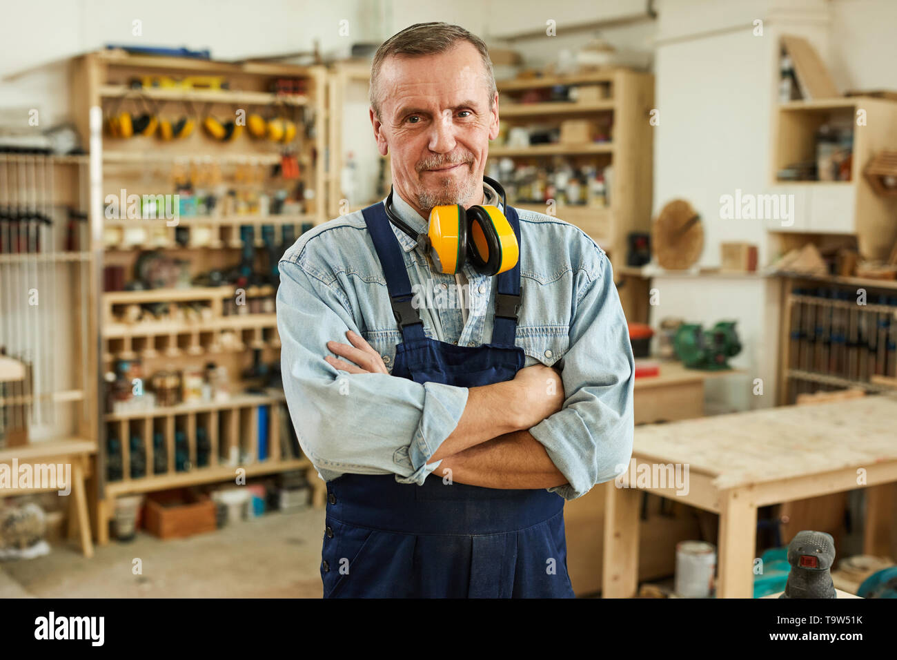 Waist up portrait of confident senior carpenter looking at camera while working in joinery, copy space - Stock Image