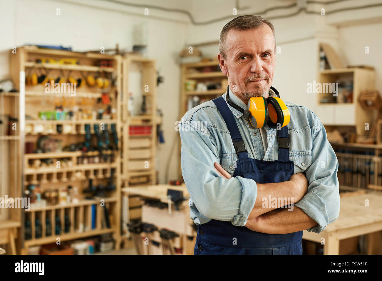 Waist up portrait of confident senior carpenter looking at camera while posing in joinery, copy space - Stock Image