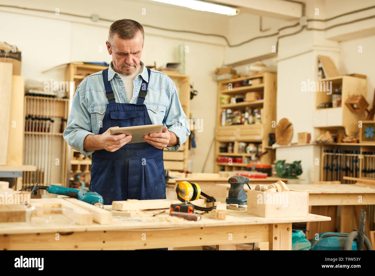 Waist up portrait of senior carpenter using tablet while working in joinery, copy space - Stock Image