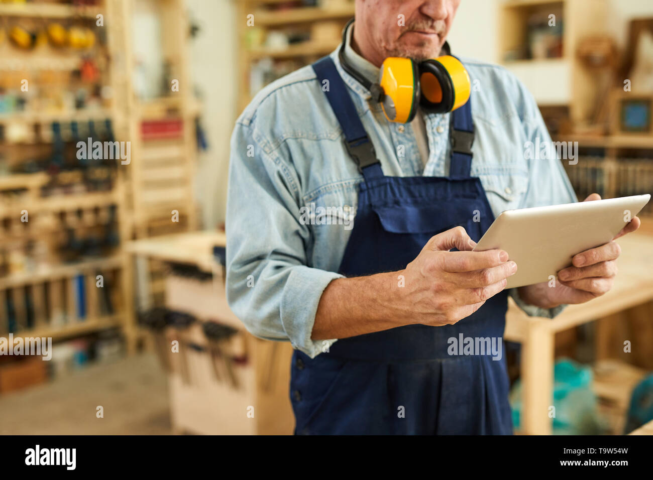 Mid section portrait of senior carpenter using tablet while working in joinery, copy space - Stock Image