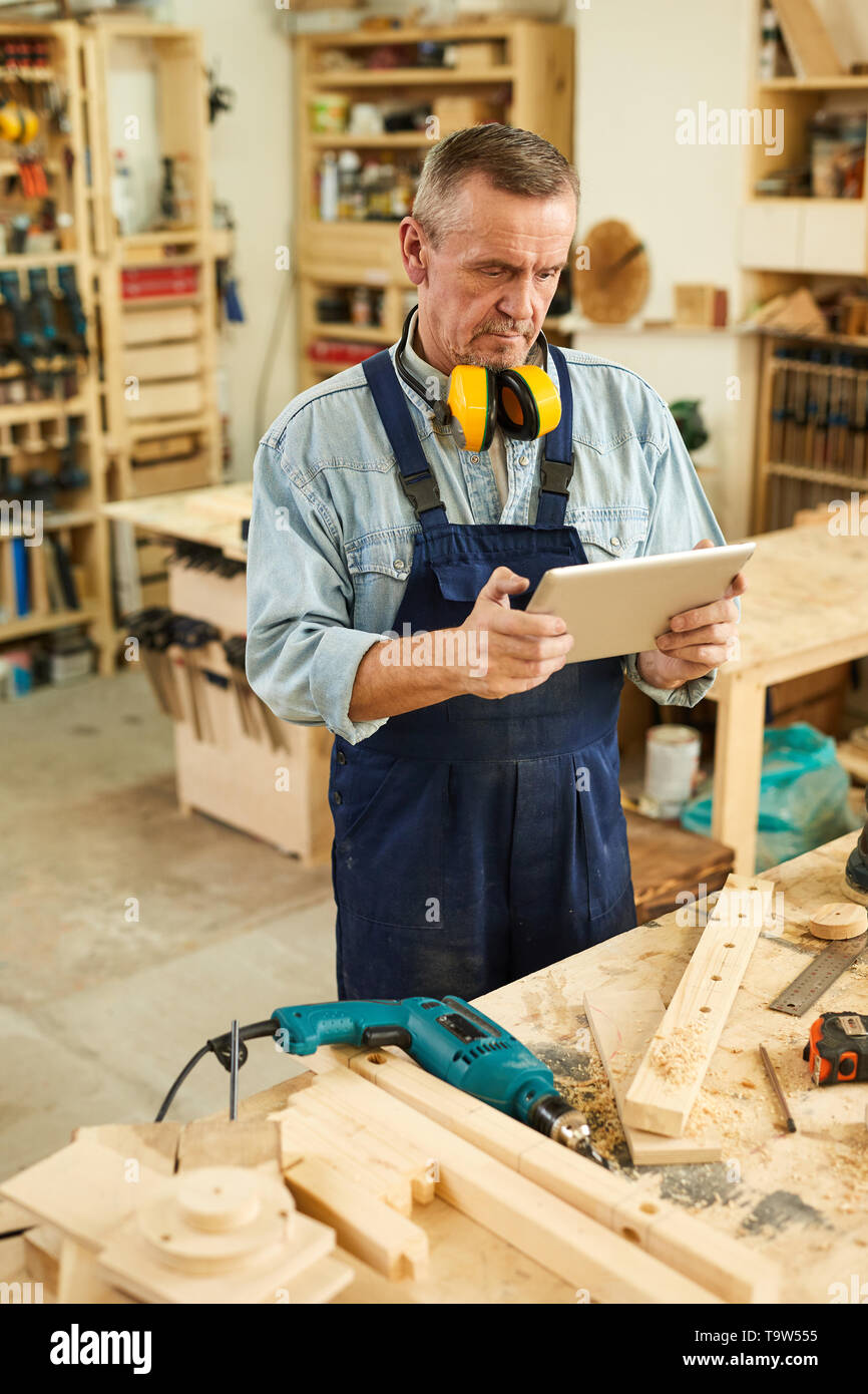 Portrait of modern senior carpenter using digital tablet while working in joinery - Stock Image