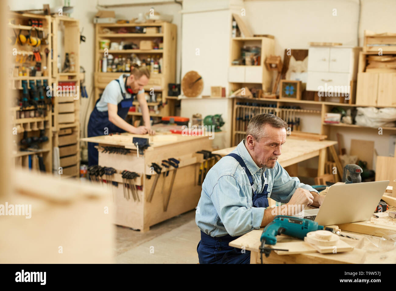 High angle portrait of two carpenters working with wood standing at tables in workshop, copy space - Stock Image