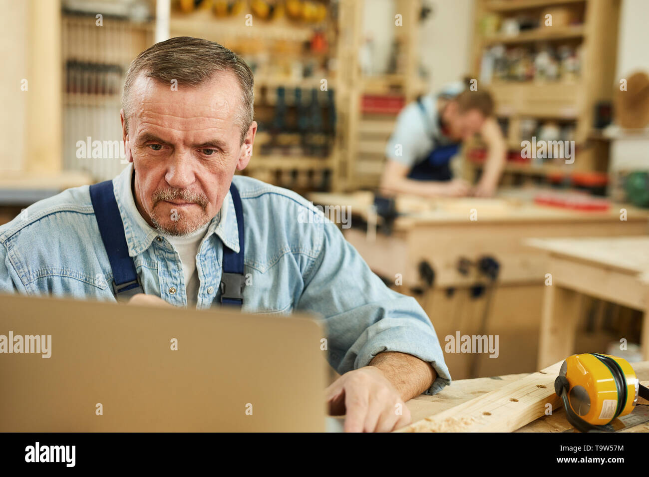Portrait of senior carpenter using laptop while working in joinery, copy space - Stock Image