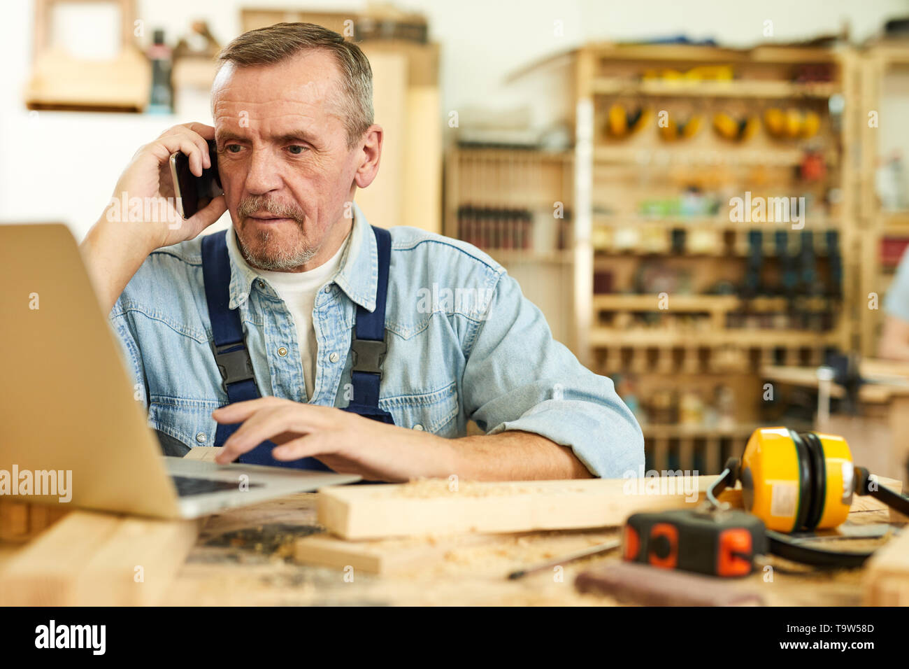 Portrait of modern senior carpenter speaking by phone and using laptop while working in joinery, copy space - Stock Image