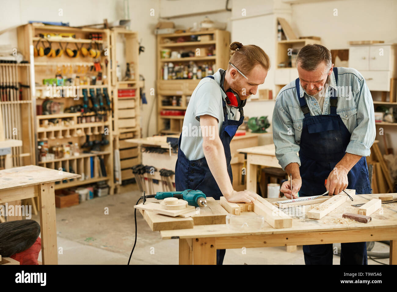 Portrait of two carpenters working with wood standing at table in workshop, copy space - Stock Image