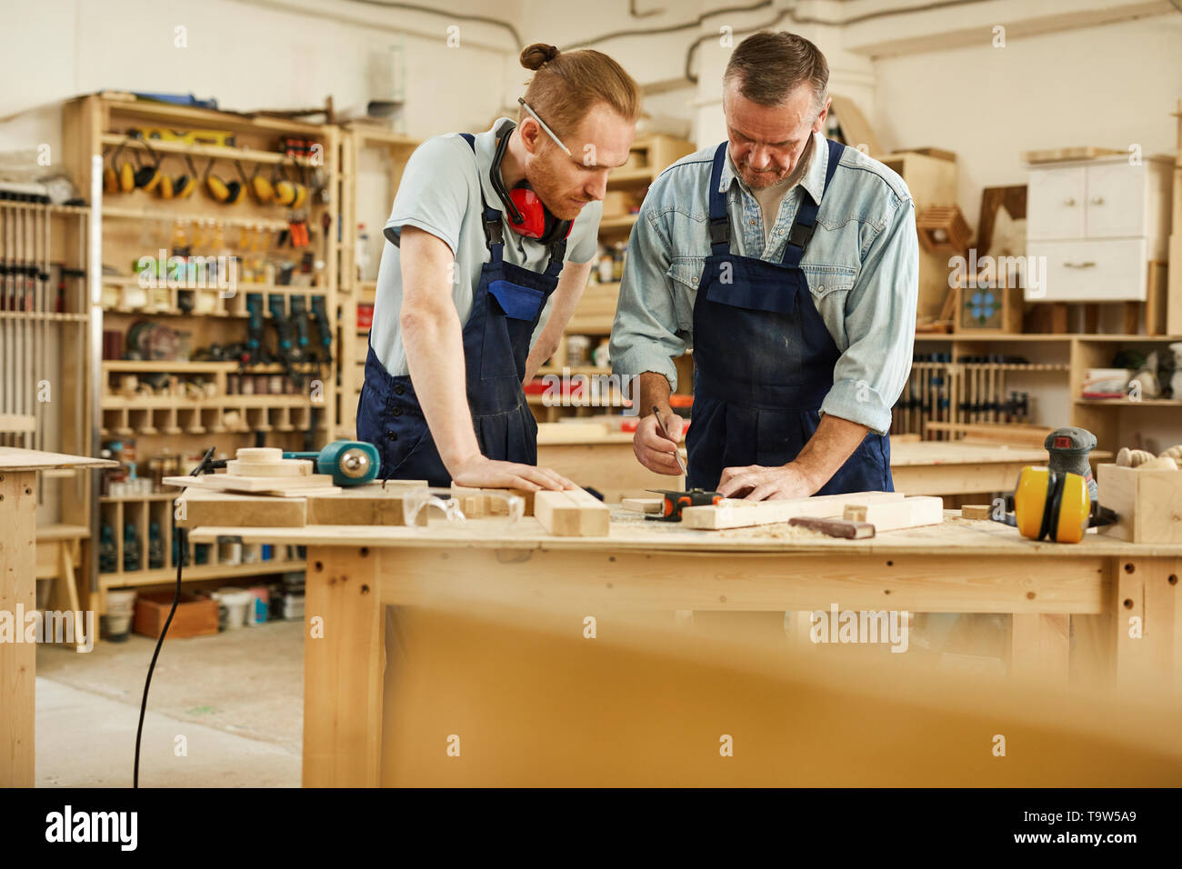 Portrait of senior carpenter teaching apprentice  standing at table in workshop, copy space - Stock Image