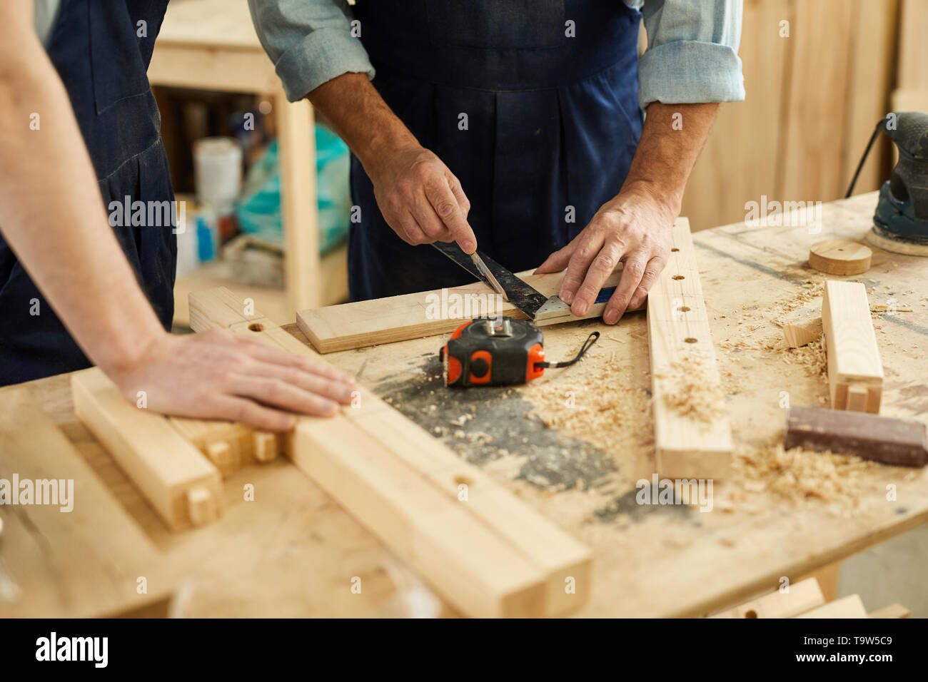 Closeup of carpenters workstation with senior man measuring wood, copy space - Stock Image
