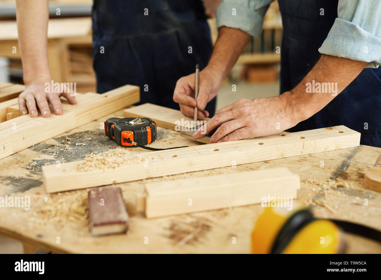 Close up of carpenters workstation with senior man measuring wood, copy space - Stock Image