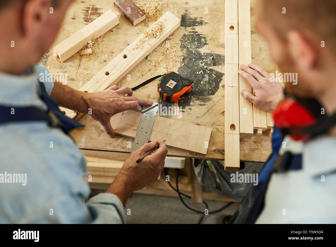 Top view  closeup of carpenters workstation with senior man measuring wood, copy space - Stock Image