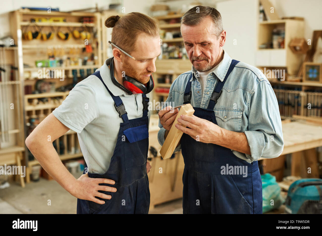 Waist up portrait of senior carpenter teaching apprentice  standing  in joinery workshop, copy space - Stock Image