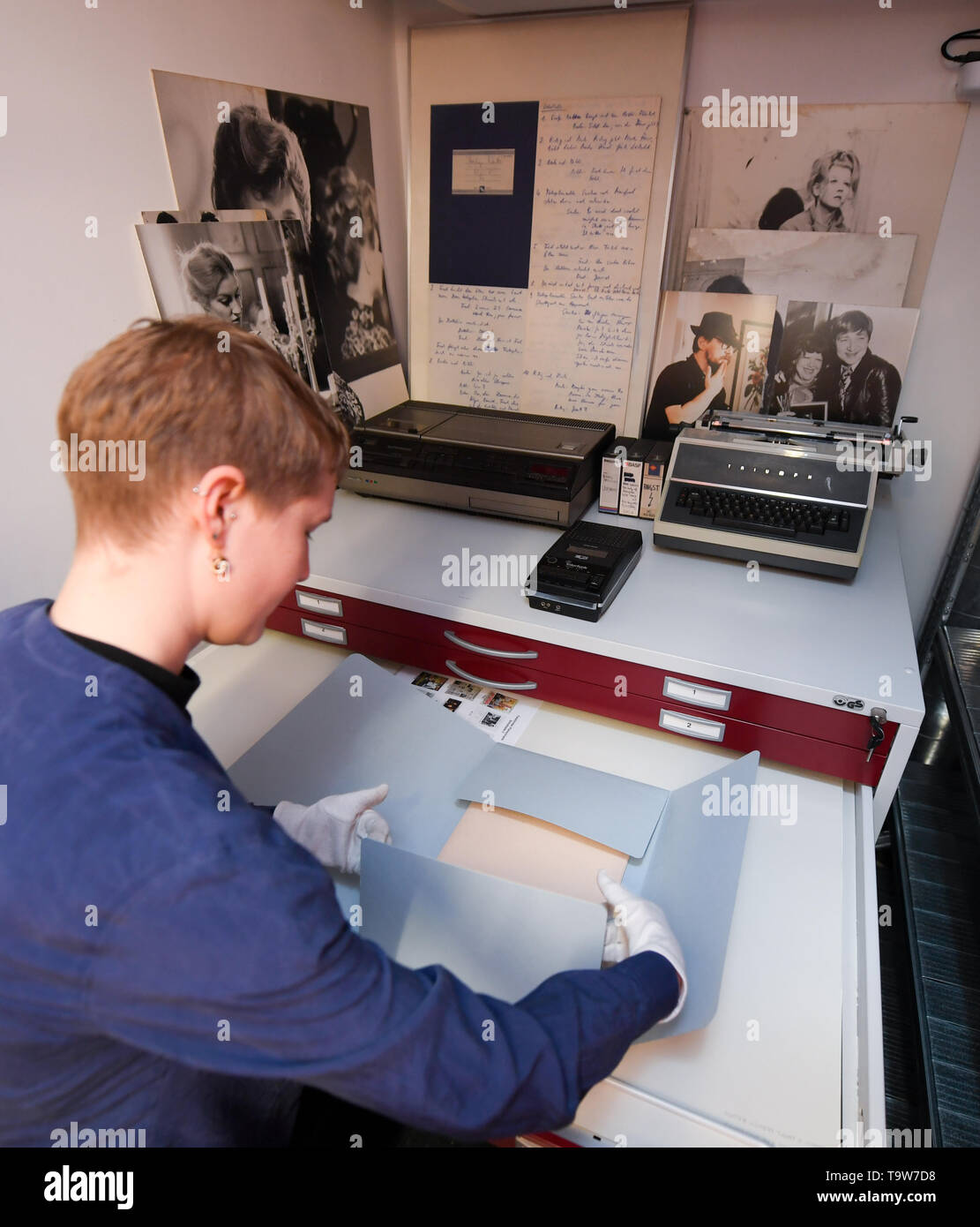 20 May 2019, Hessen, Frankfurt/Main: Susanne Mohr, a student assistant, is standing in the written records and photo archive of the new Fassbinder Center of the DFF - Deutsches Filminstitut und Filmmuseum - in front of a poster cabinet on which a video recorder, a cassette recorder and a typewriter are placed. The late director Rainer Werner Fassbinder had a decisive influence on German film. Much of his estate is now accessible. It includes scripts, financing plans, shooting plans, contracts, production files and correspondence. Photo: Arne Dedert/dpa - Stock Image