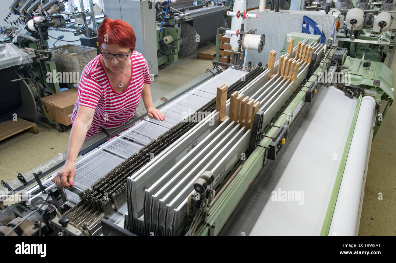 Crimmitschau, Germany. 20th May, 2019. Beate Eichler works at Spengler und Fürst in Crimmitschau on a weaving machine which, among other things, is used to produce technical textiles. Saxony is one of the most important centres of the German textile and clothing industry. The domestic textile industry consists of a large number of specialised companies, which also have their footholds in vehicle construction, structural and civil engineering, mechanical engineering and the health industry. Credit: Hendrik Schmidt/dpa-Zentralbild/ZB/dpa/Alamy Live News - Stock Image