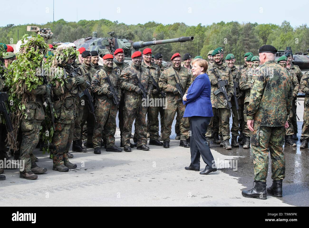 Munster, Germany. 20th May, 2019. German Chancellor Angela Merkel (2nd R, Front) talks with members of NATO'S Very High Readiness Joint Task Force during her visit in Munster, Germany, on May 20, 2019. Merkel on Monday assured Germany's help for Ukraine to solve the conflicts in its Donbas region. She made the statement during her visit to a rapid reaction force of NATO in Germany's Munster. Credit: Shan Yuqi/Xinhua/Alamy Live News - Stock Image