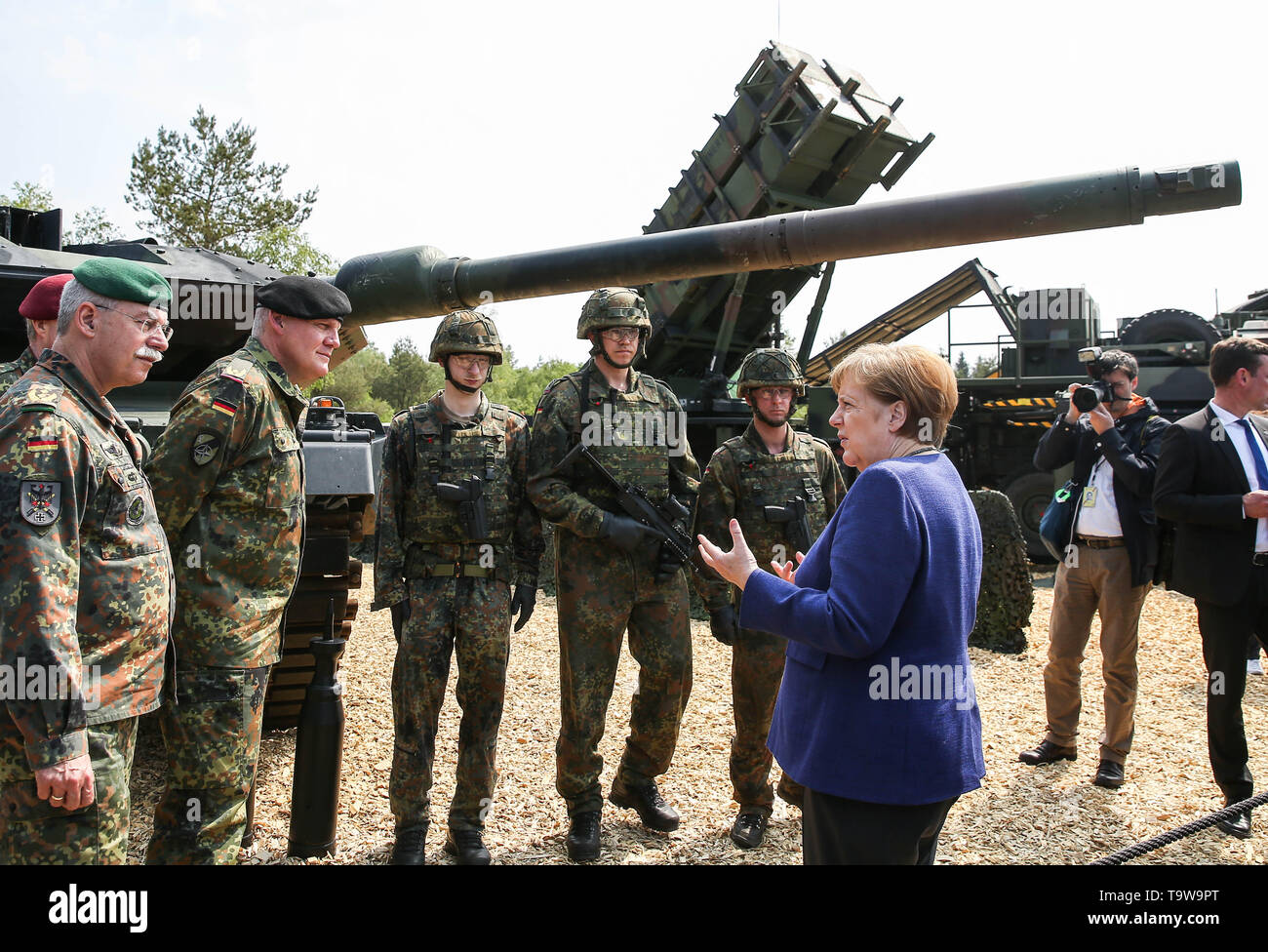 Munster, Germany. 20th May, 2019. German Chancellor Angela Merkel (R, Front) talks with members of NATO'S Very High Readiness Joint Task Force during her visit in Munster, Germany, on May 20, 2019. Merkel on Monday assured Germany's help for Ukraine to solve the conflicts in its Donbas region. She made the statement during her visit to a rapid reaction force of NATO in Germany's Munster. Credit: Shan Yuqi/Xinhua/Alamy Live News - Stock Image