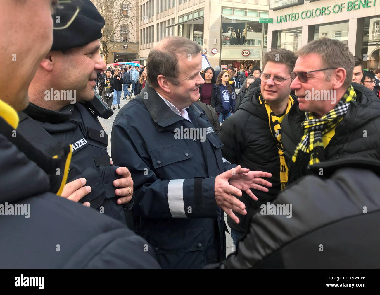 Munich, Germany. 17th May, 2019. Police chaplain Andreas Simbeck (M) talks to the leader of the police mission hundred, Dieter Winklmaier (l), with football fans. (to dpa-KORR ''It's about getting rid of it' - That's how police chaplains work') Credit: Wera Engelhardt/dpa/Alamy Live News - Stock Image