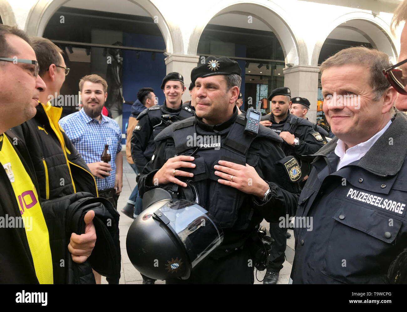 Munich, Germany. 17th May, 2019. Police chaplain Andreas Simbeck (r) talks to the leader of the police mission hundred, Dieter Winklmaier (M), with football fans. (to dpa-KORR ''It's about getting rid of it' - That's how police chaplains work') Credit: Wera Engelhardt/dpa/Alamy Live News - Stock Image