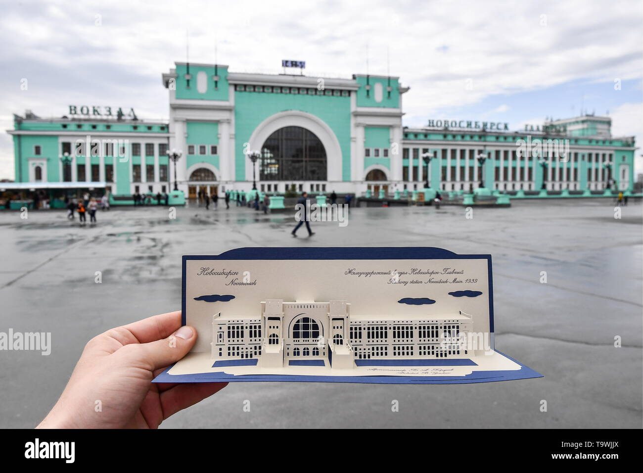 Novosibirsk, Russia. 21st May, 2019. NOVOSIBIRSK, RUSSIA - MAY 21, 2019: Comparing the Novosibirsk Railway Station building and its Kirigami postcard model made by architect Nikita Kutenkov at home; Kirigami is an art of creative paper cutting and folding. Kirill Kukhmar/TASS Credit: ITAR-TASS News Agency/Alamy Live News - Stock Image