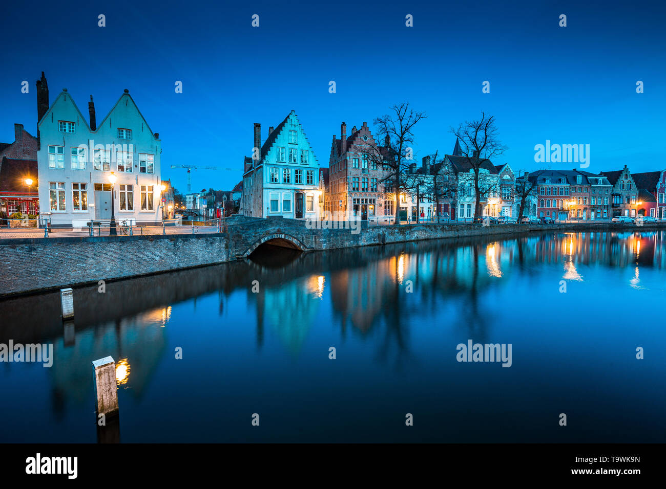 Beautiful twilight view of the historic city center of Brugge with old houses along famous Potterierei canal illuminated during blue hour at dusk, Bru - Stock Image