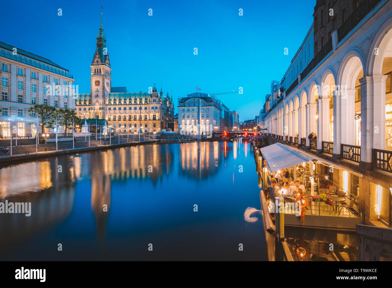 Classic twilight view of Hamburg city center with historic town hall reflecting in Binnenalster during blue hour at dusk, Germany - Stock Image