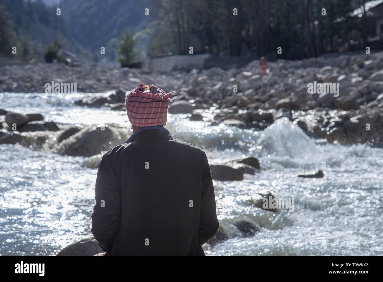 Senior man, standing beside mountain river, looking at view - Stock Image