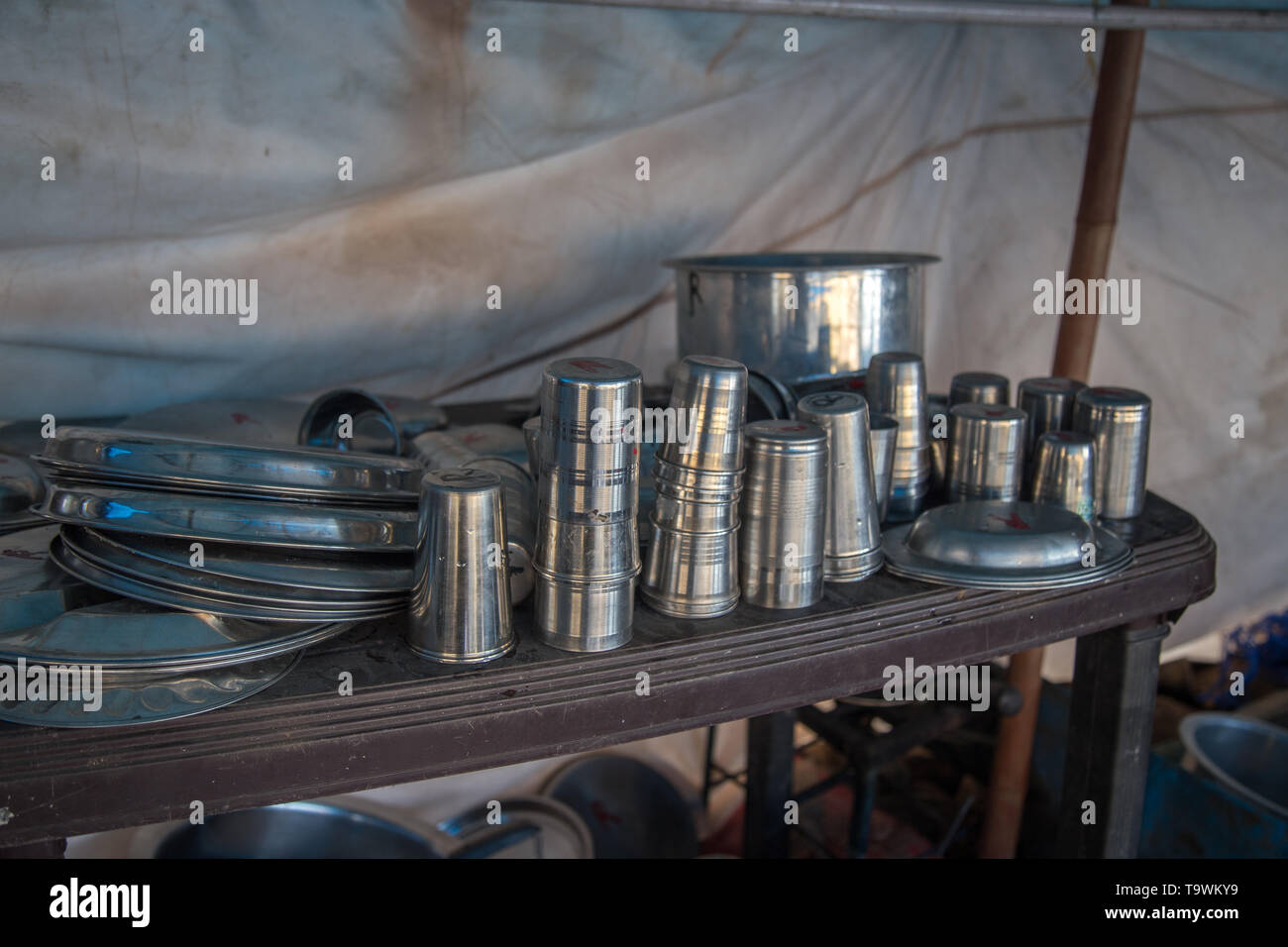 Close up of steel utensils bowls, pots and trays used by an old open kitchen restaurant in India - Stock Image