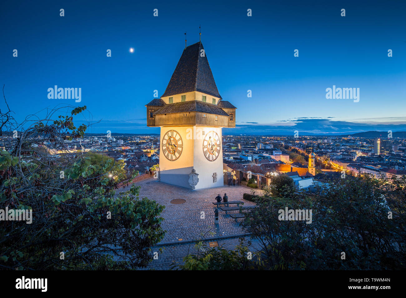 Beautiful twilight view of famous Grazer Uhrturm (clock tower) illuminated during blue hour at dusk, Graz, Styria region, Austria - Stock Image