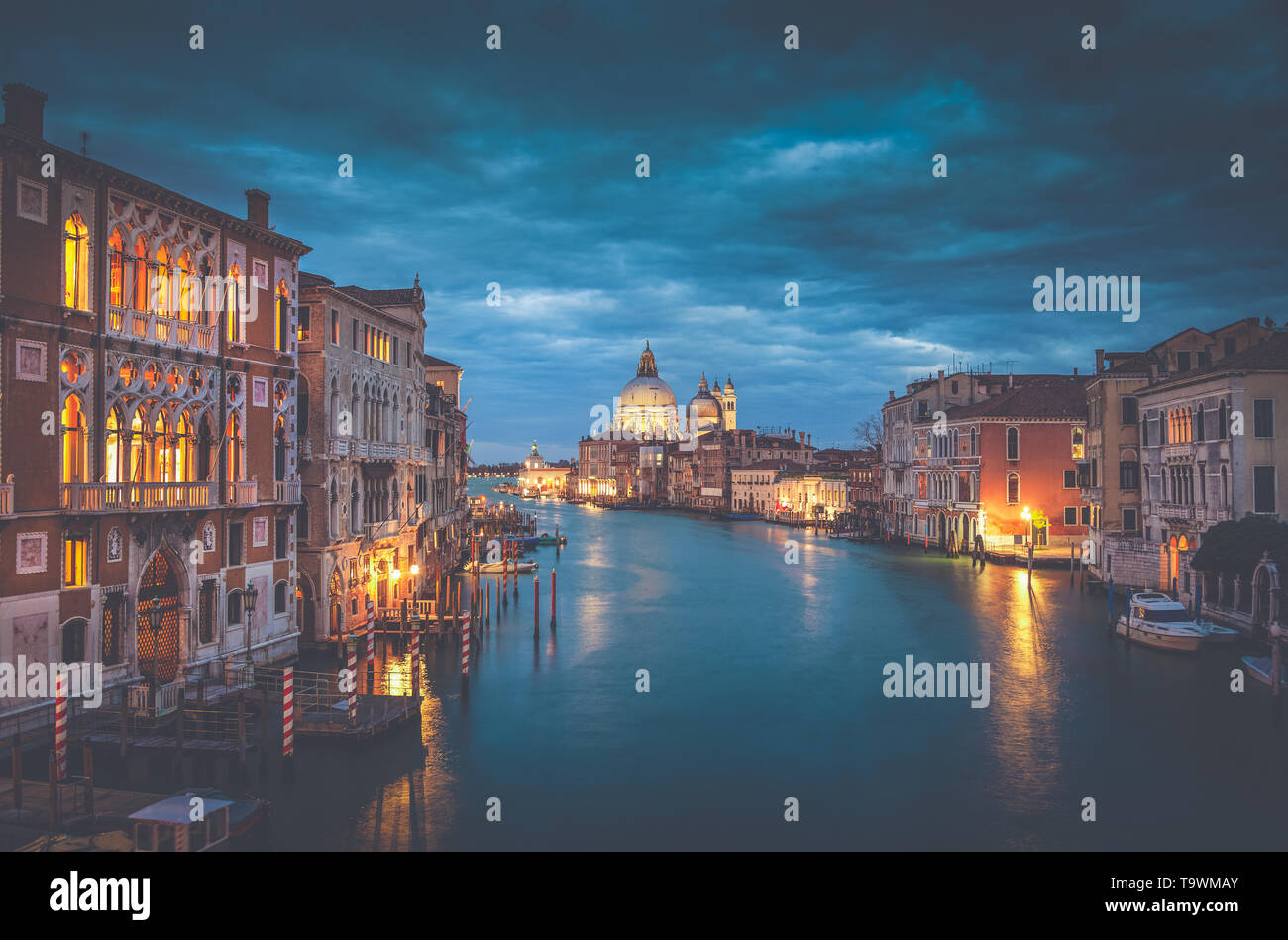 Classic view of famous Canal Grande with historic Basilica di Santa Maria della Salute in the background in beautiful mystic post sunset twilight with - Stock Image