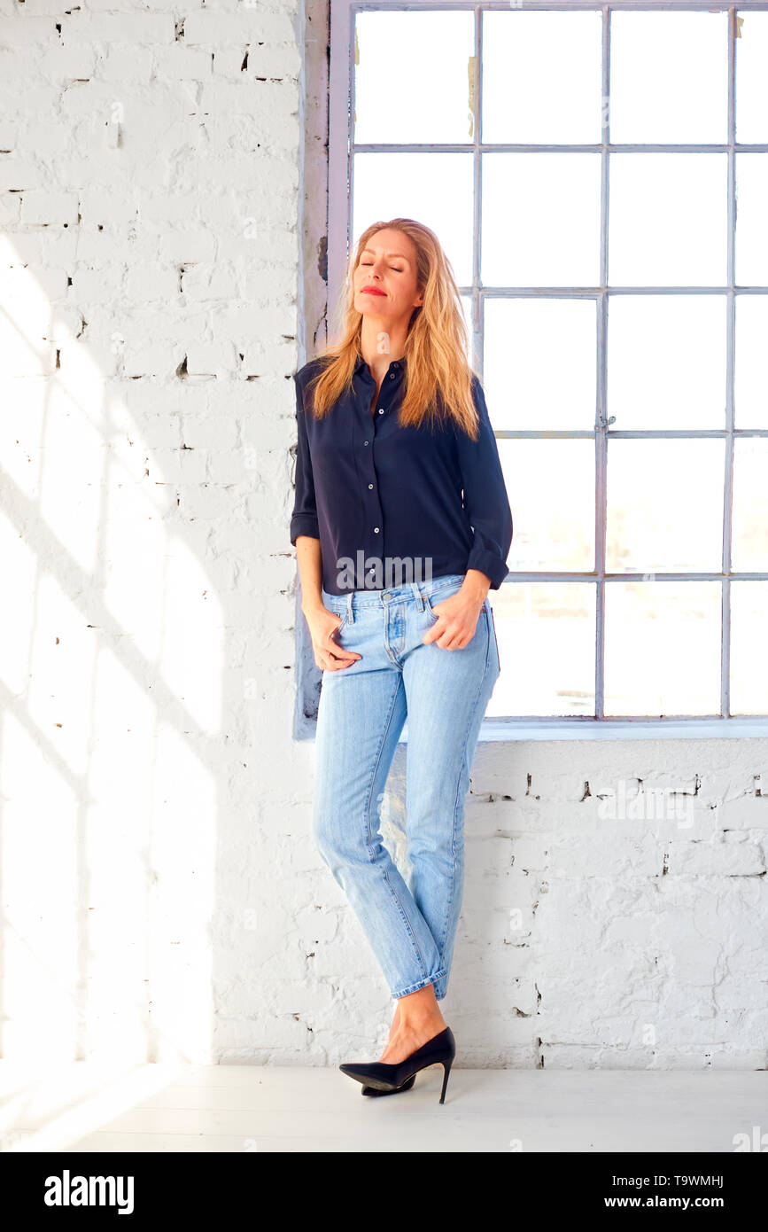 Full length shot of beautiful blond woman wearing shirt and jeans while standing at the window and daydreaming. - Stock Image