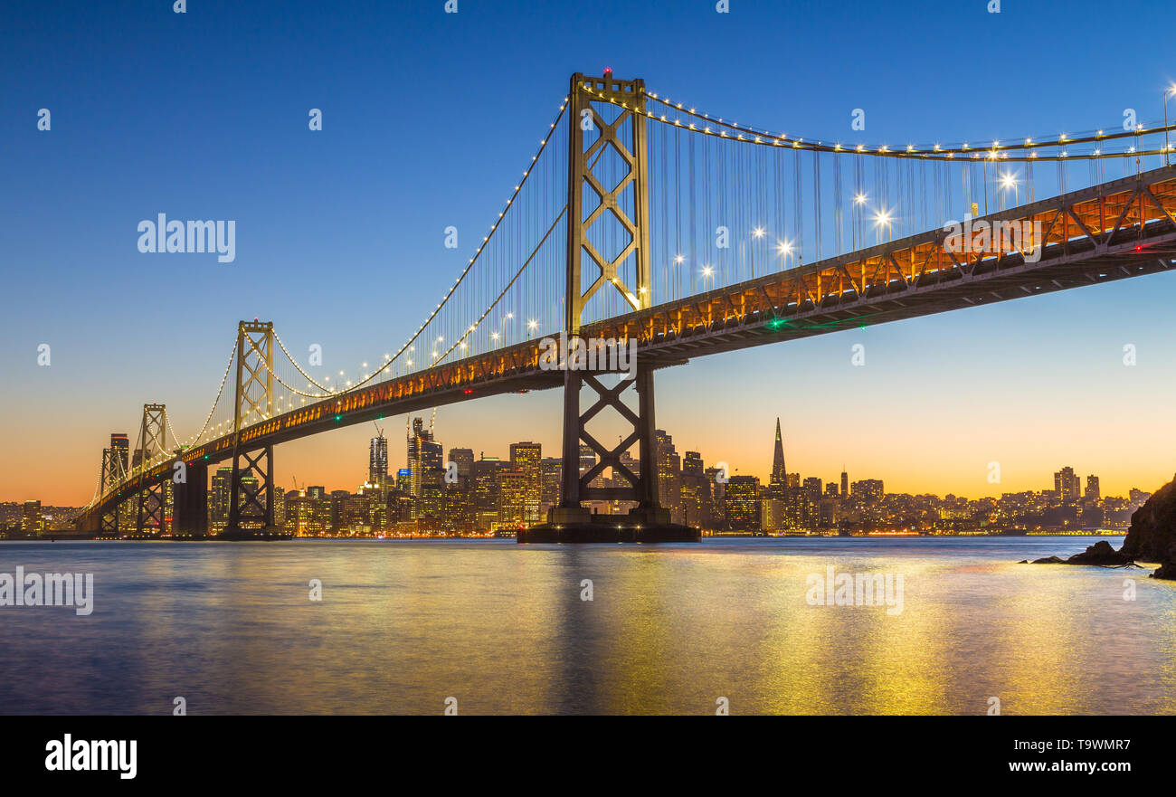 Classic panoramic view of famous Oakland Bay Bridge with the skyline of San Francisco illuminated in beautiful twilight after sunset in summer, Califo - Stock Image