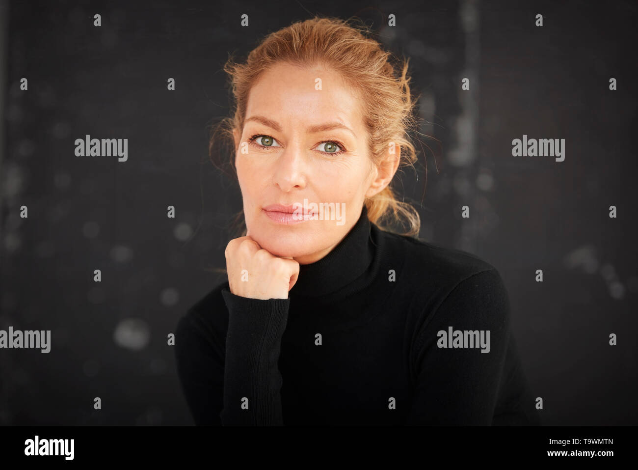 Portrait of beautiful mature woman wearing roll neck sweater and looking at camera while sitting with hand on chin at dark background. - Stock Image