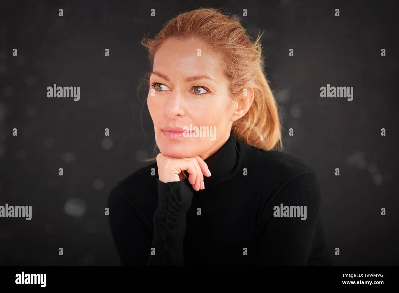 Close-up portrait shot of beautiful blond mature woman sitting at dark background while daydreaming. - Stock Image
