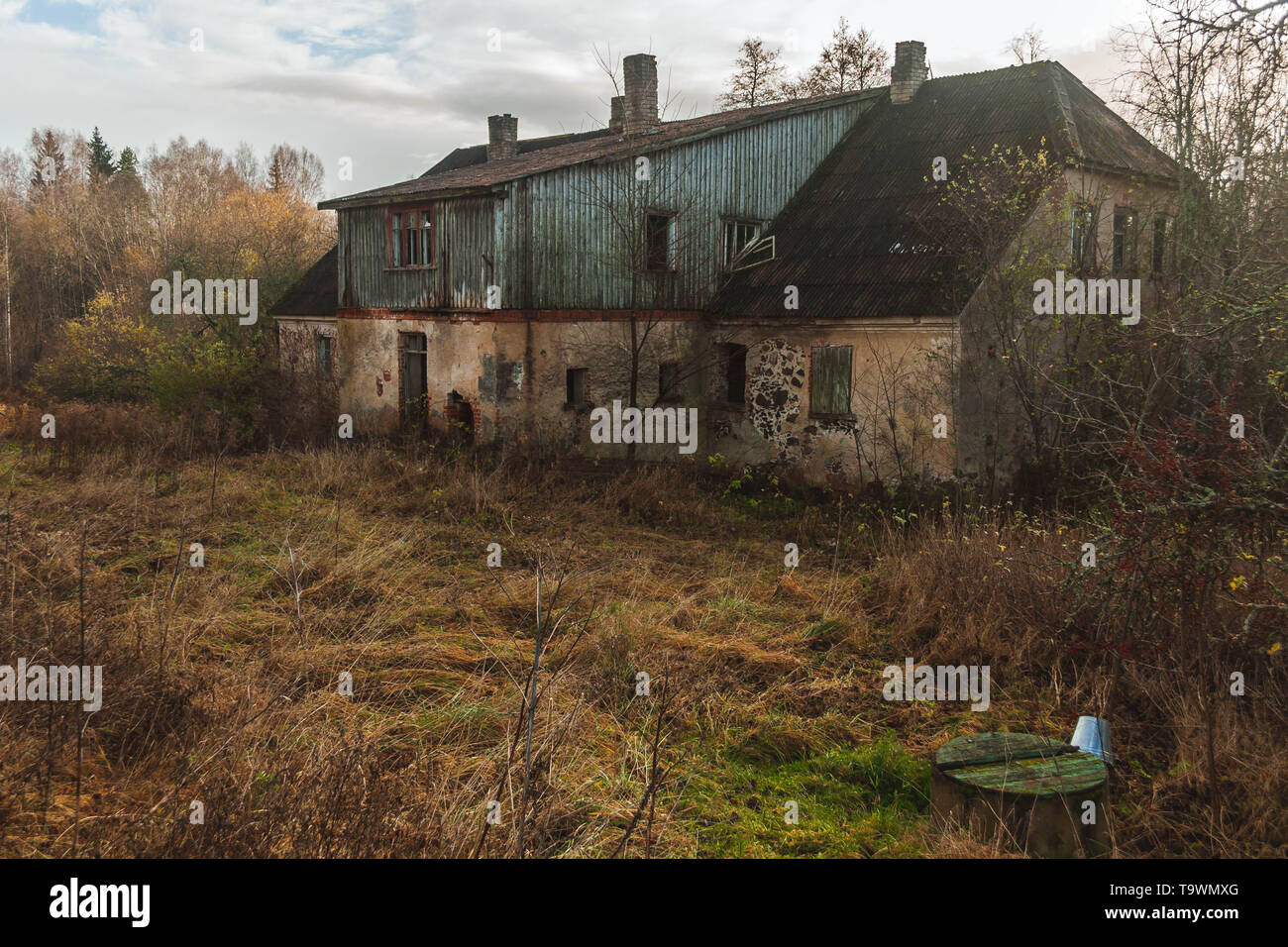 Dilapidated and abandoned former distillery from manor times in Kaleši, Latvia, and old well with metal bucket. - Stock Image