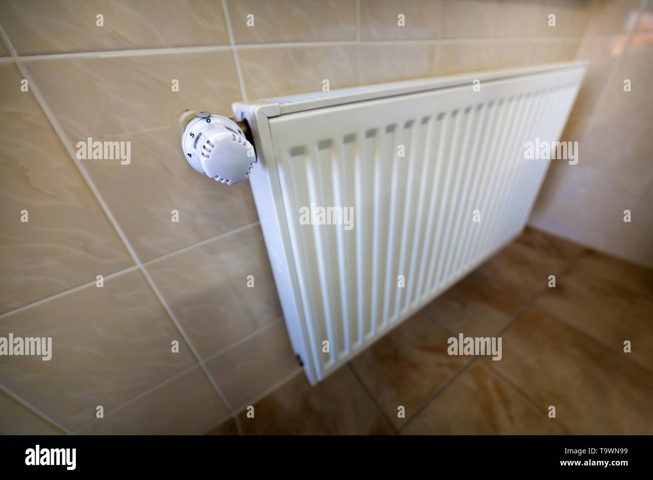 Close-up of white heating radiator with thermostat valve ion tiled walls and floor background. Comfortable warm home interior, climate control, money  - Stock Image