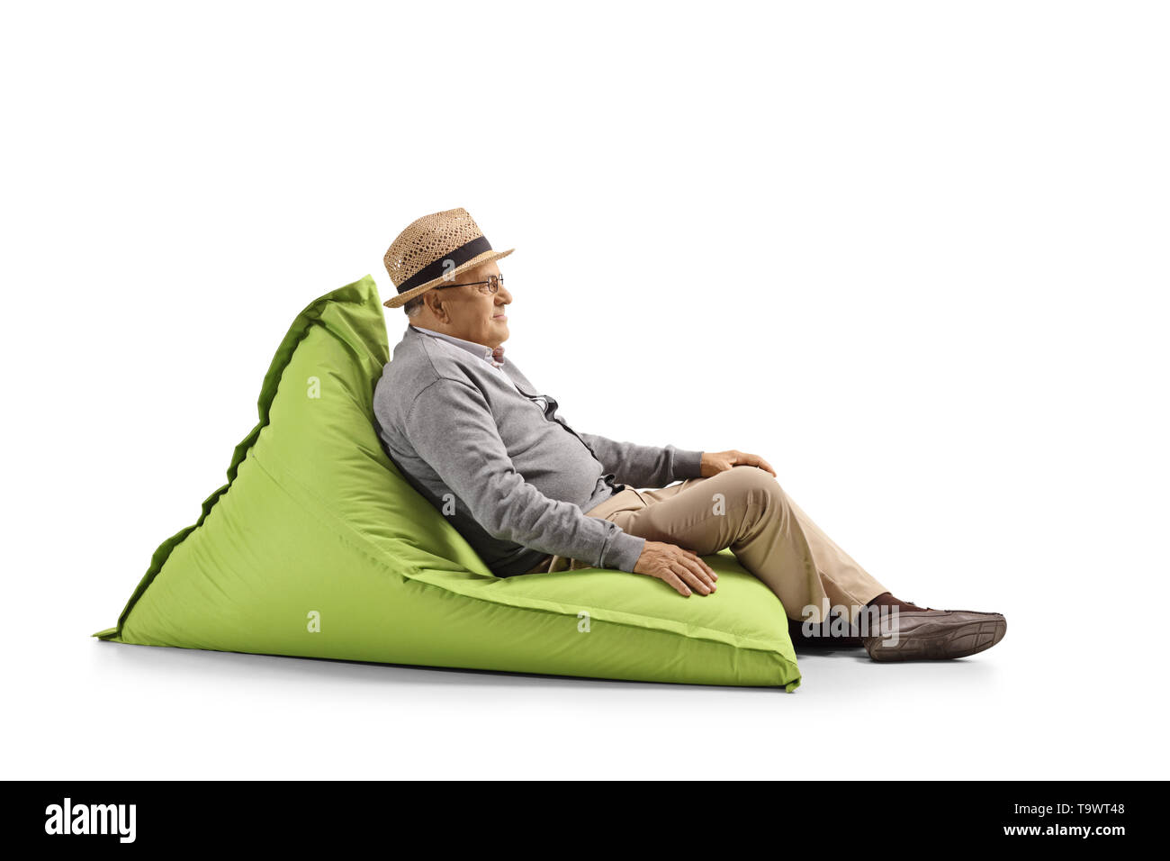 Full length shot of a senior gentleman resting on a bean-bag chair isolated on white background - Stock Image