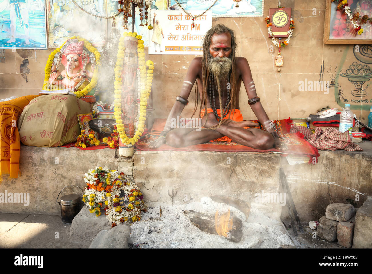 Sadhu baba at Varanasi sitting in meditation posture with holy fire burning at the Ganges river ghat - Stock Image