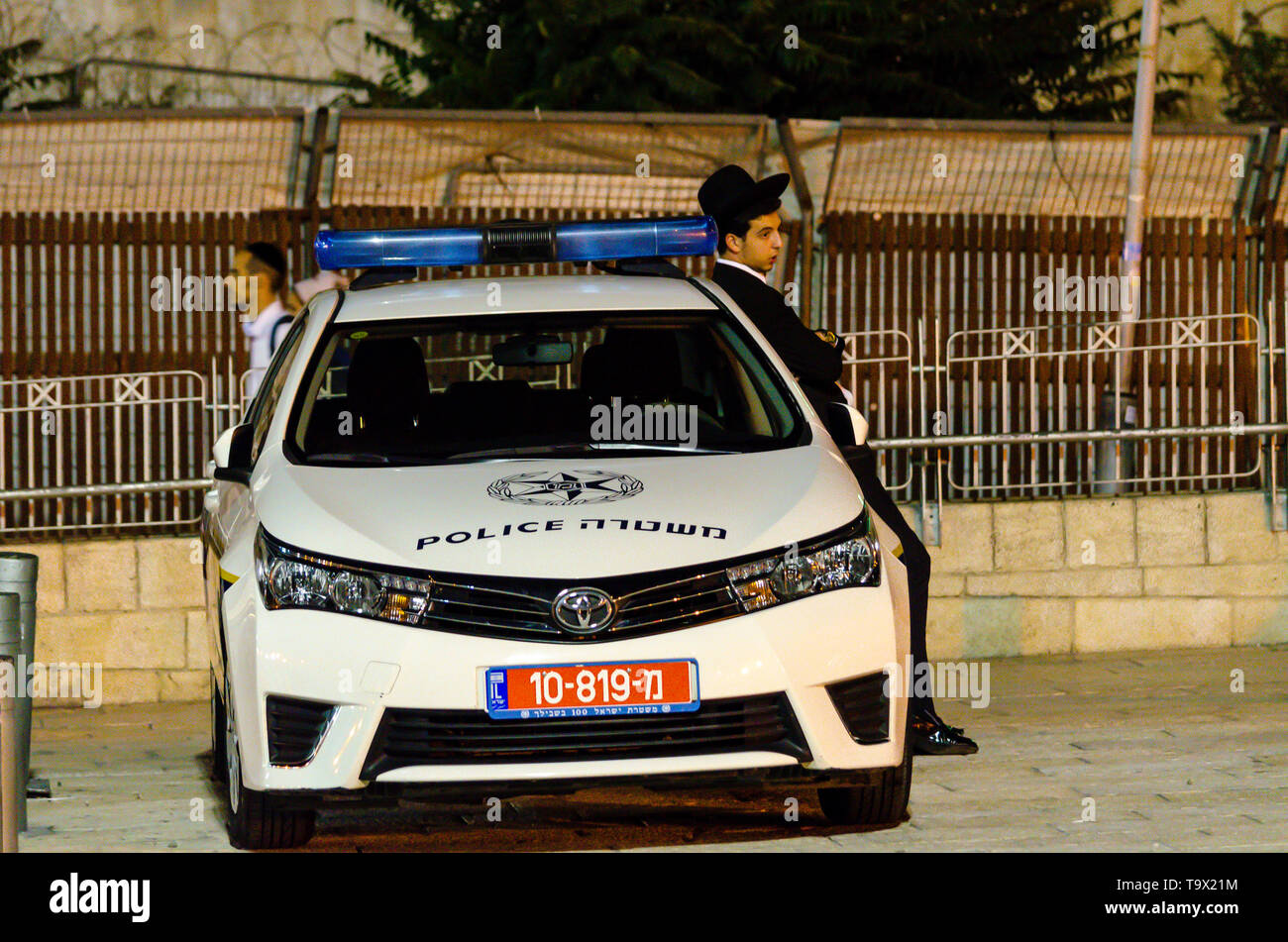 Jerusalem, Israel- August 17, 2016: Young Jewish Orthodox man leaning on police car outside the Dung Gate in the Old City of Jerusalem, Israel - Stock Image