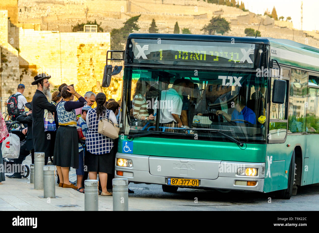 Jerusalem, Israel- August 17, 2016: Group of orthodox Jews waiting to get on a public transit bus at the Dung Gate bus stop in Old City of Jerusalem - Stock Image