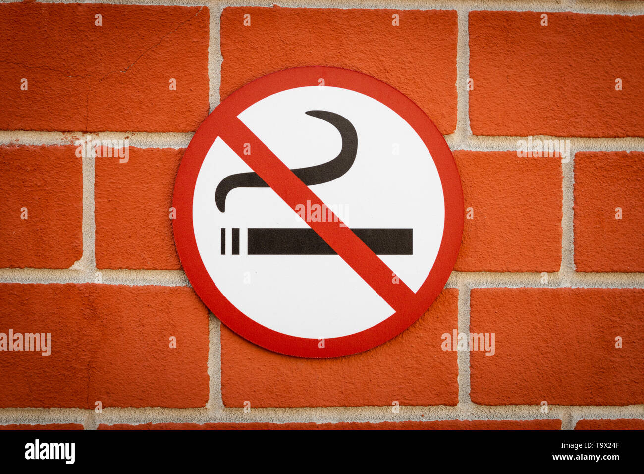 no smoking sign against brickwall in European city - Stock Image