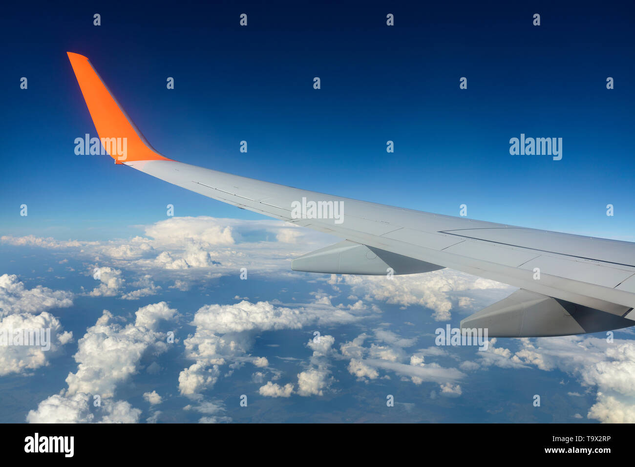 Wing of an airplane flying over white clouds in a blue sky Stock Photo