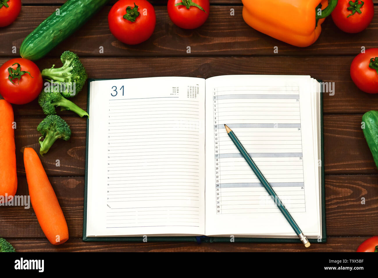 Diet regimen, vegetable image and diet menu plan on Notepad. The guy is recording a dietary program. new cooking recipes - Stock Image