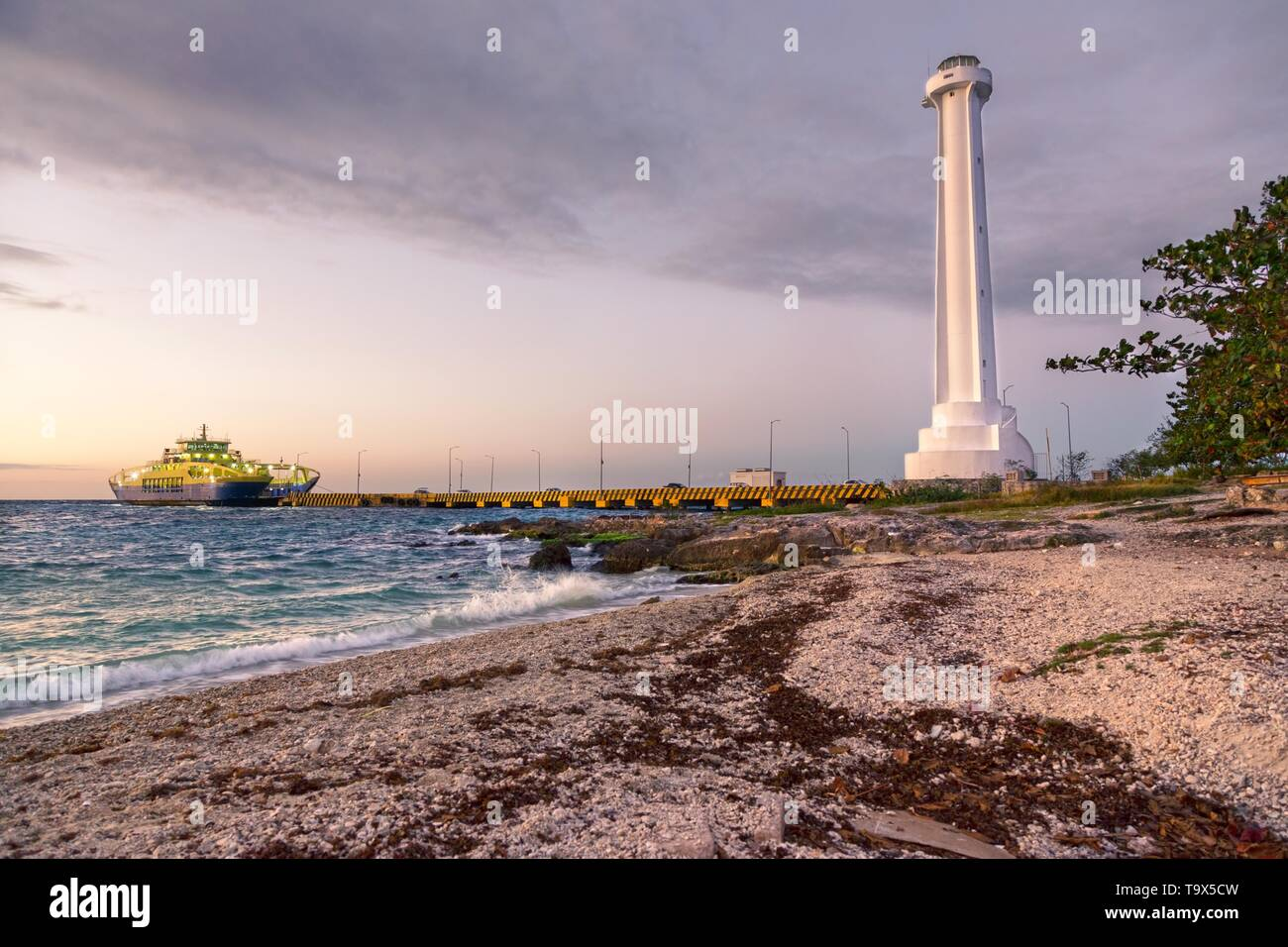 Dramatic Sunset Sky Colors over Caribbean Beach and Car Ferry Pier Lighthouse in Cozumel, Mexico Yucatan Peninsula Stock Photo